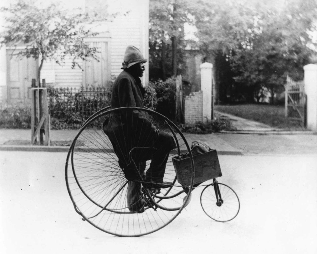 Man riding Victor Tricycle Company tricycle at unidentied location in Georgetown, c. 1890-1900.