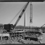 Photo shows heavy machinery and piers used in early stages of construction.